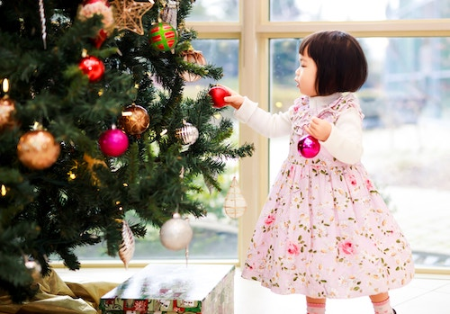 The image has a christmas tree with a small kid next to it. Used for a blog post on how to make money as a kid