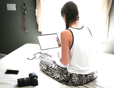 woman siting with the laptop on bed entering data