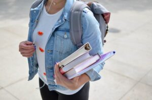 things to sell at school - blog graphic - girl walking to school with books in hand